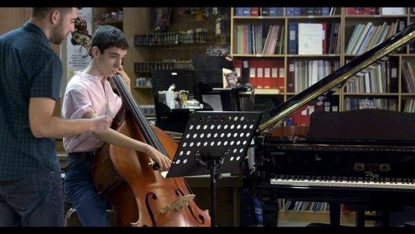 Momento del cortometraje El solista de la orquesta, afinando el contrabajo